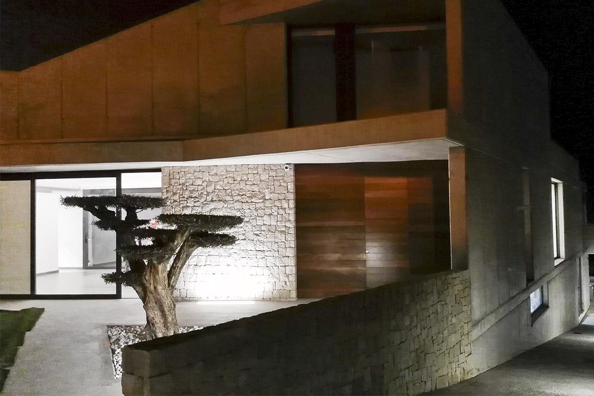 construcción de vivienda en hormigón visto y piedra elo construcciones fachada de noche