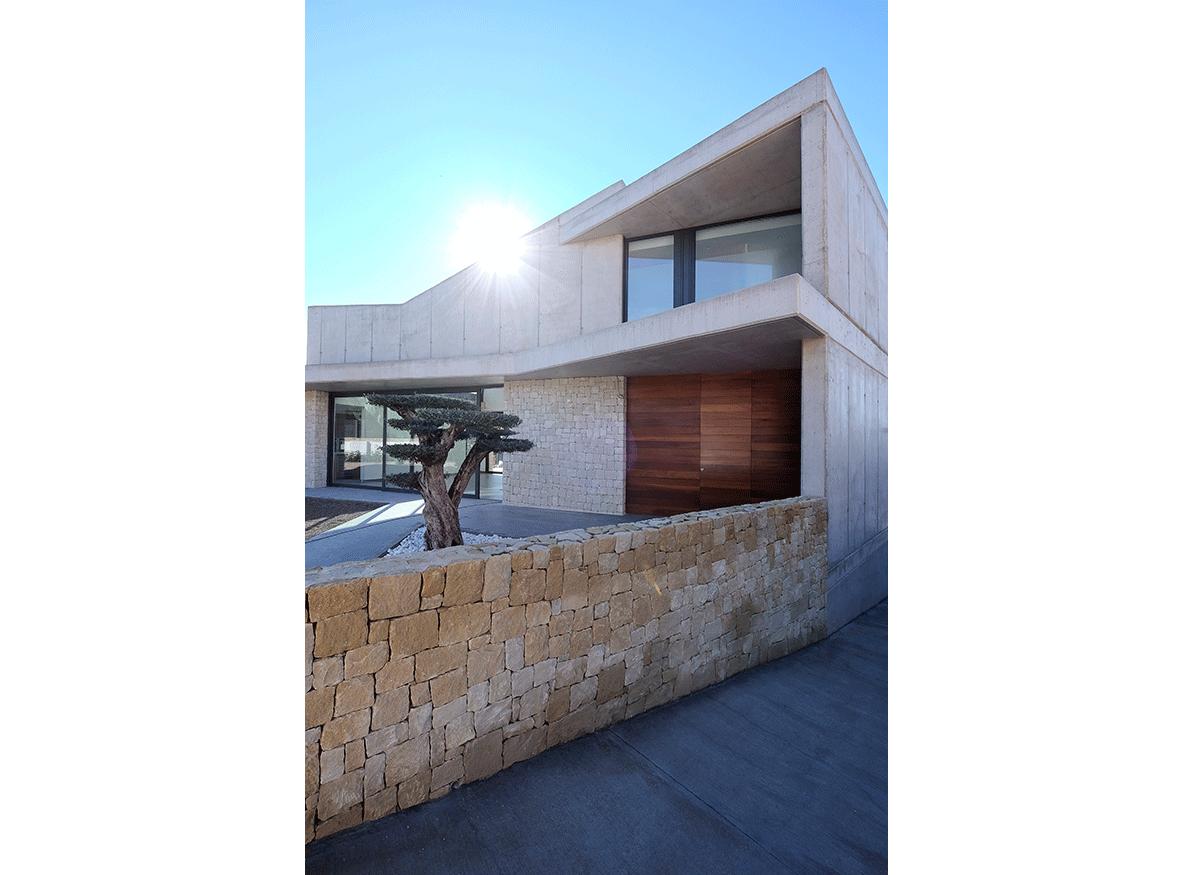 construcción de vivienda en hormigón visto y piedra elo construcciones fachada principal