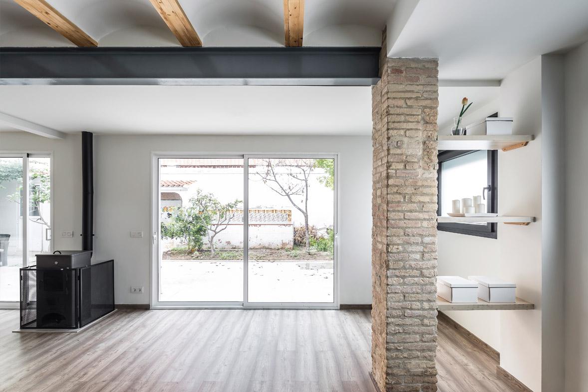 Reforma integral de vivienda salón comedor vistas al patio chimenea pilar ladrillo antiguo